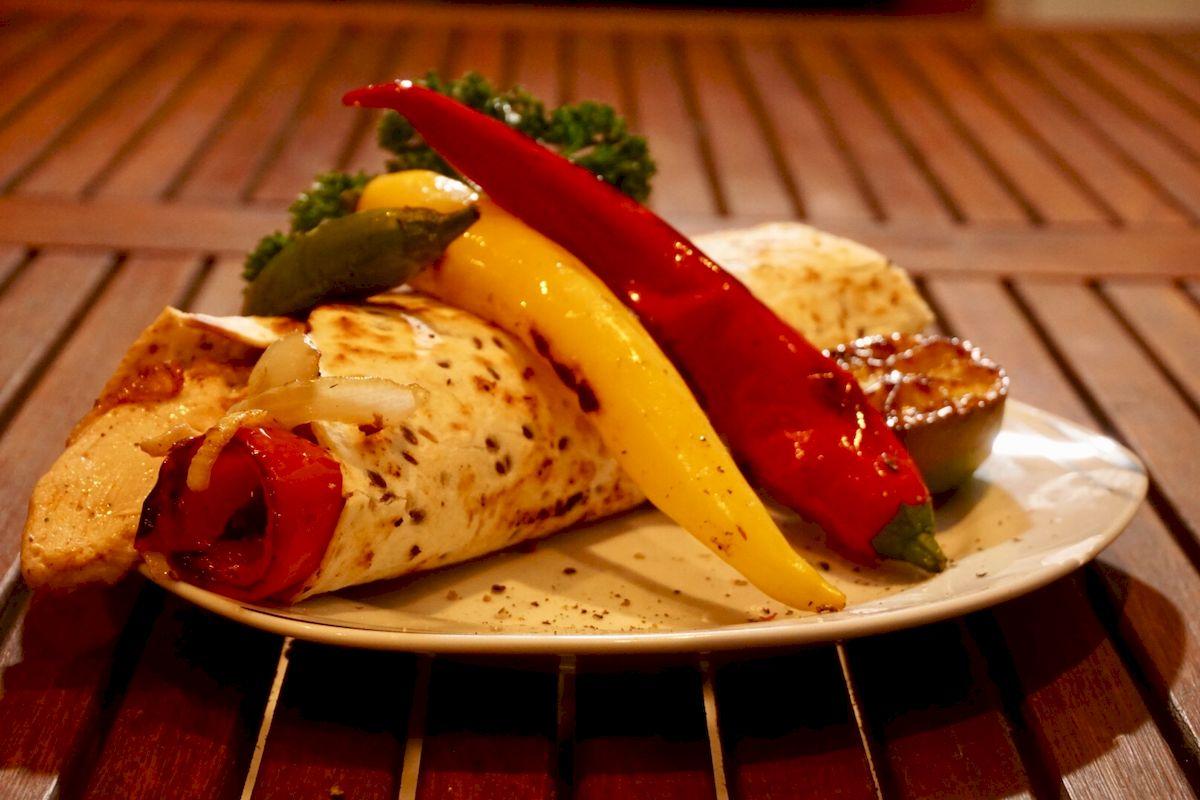 Burrito von der Feuerplatte mit Hähnchen, Paprika und Zwiebeln